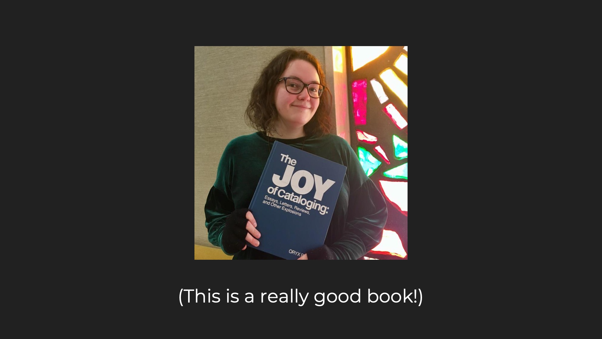 Picture of me holding the book 'The Joy of Cataloguing' by Sanford Berman, captioned 'This is a really good book!'